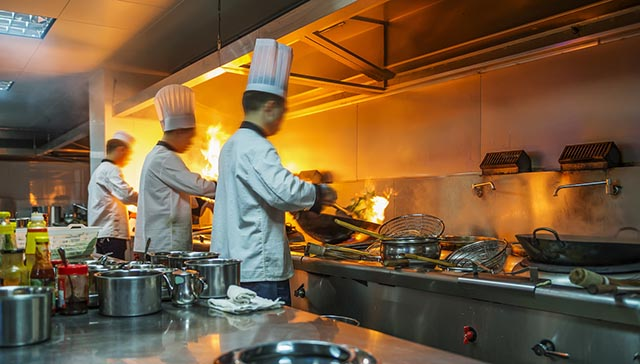 Chef In Restaurant Kitchen At Stove With Pan, Doing Flambe On Fo